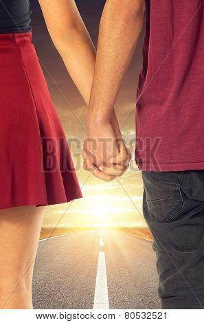 Couple of sweethearts holding hands and walking together in a road into the sun