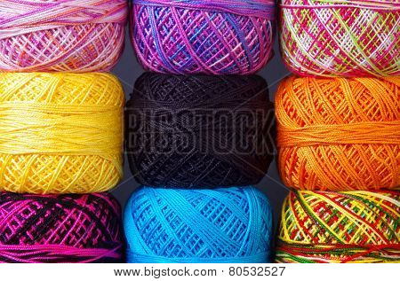 A pile of colorful yarn coils over grey background