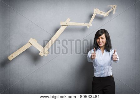 Concept: Succeeding in career or business. Young happy businesswoman holding thumbs up in front of positive trend graph,  isolated on grey background.
