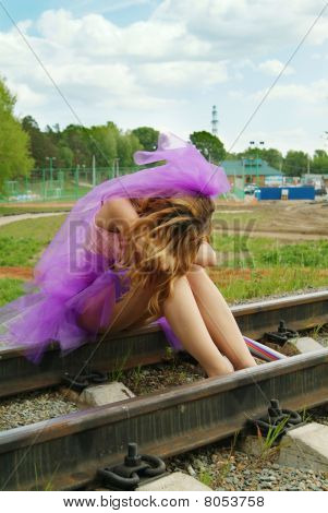 Beauty Girl Sitting On The Rail