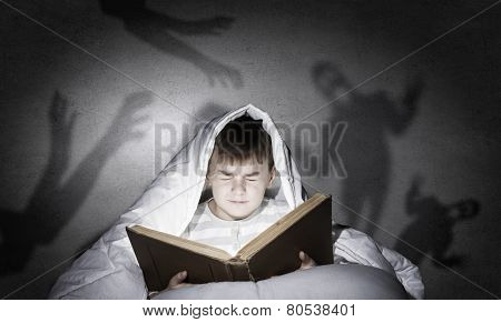 Little cute boy sitting in bed under blanket with book