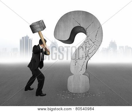 Businessman Holding Hammer Cracked Question Mark With Gray Cityscape Background