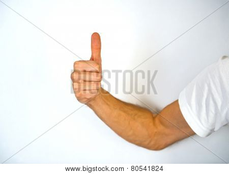 Close up view of the hand of a man giving a thumbs up gesture of approval and success with his knuckles towards the camera and arm extended from the side, isolated on white