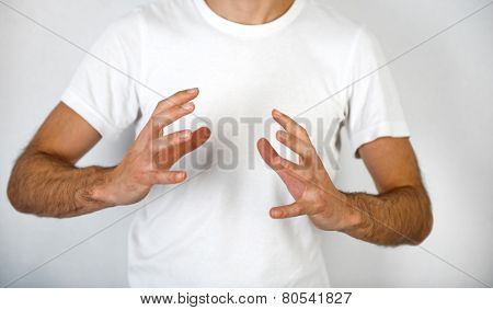 Man making a hand gesture to clasp a round object with his hands on opposite sides and fingers spread, blank space in between over his white t-shirt