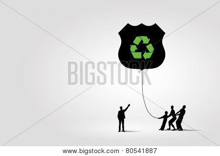 Silhouettes of people pulling balloon with recycle sign