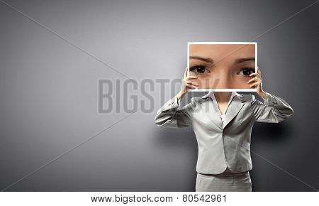 Unrecognizable businesswoman holding big photo with eyes