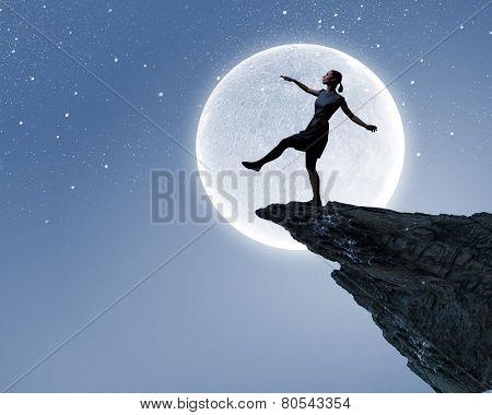 Young woman walking at mountain edge at night