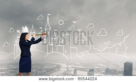 Young businesswoman in paper crown looking in spyglass