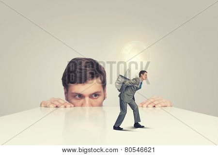 Businessman peeping from under table at overloaded worker