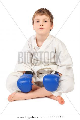 Little Boxer Boy In White Dress And Blue Boxing Gloves Sitting Isolated On White