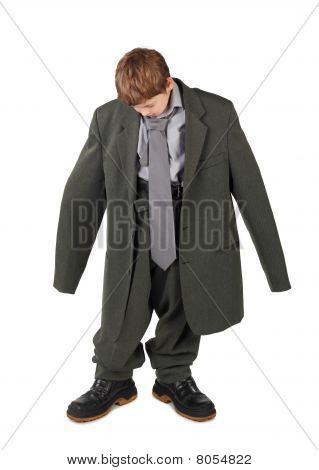 Little Boy In Big Grey Man's Suit And Boots Looking At Floor Isolated On White Background