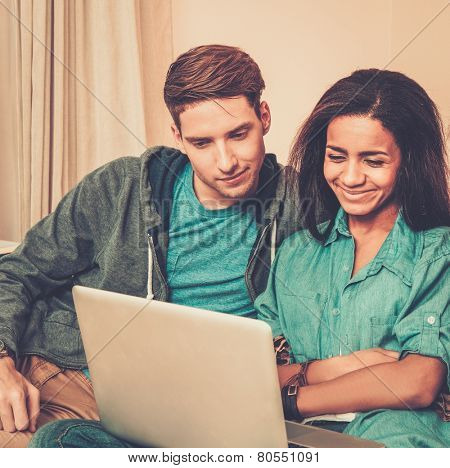 Young multi ethnic students couple preparing for exams in home interior