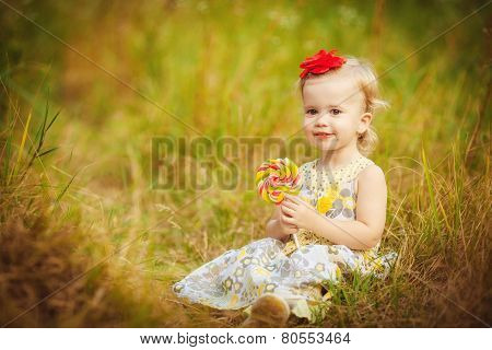 Little girl in the summer park with a lollipop in her hand.