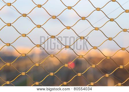 Blurred Cityscape Beyond Golden Fence