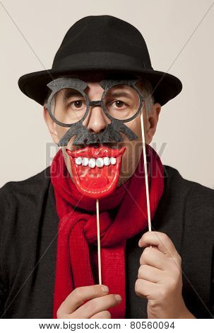Cheerful man in a carnival mask and a black hat