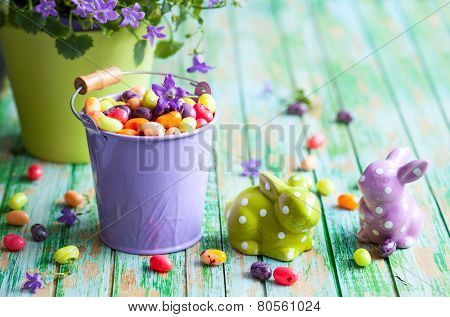 Easter rabbits and buckets with jelly beans on the vintage wooden table