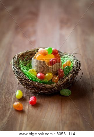 colorful Easter candy eggs in nest on the wooden table
