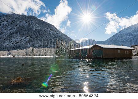 sunbeams over austrian lake in snowy winter landscape