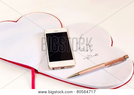 Smartphone And Valentine Love Message In Heart Shape Notebook.