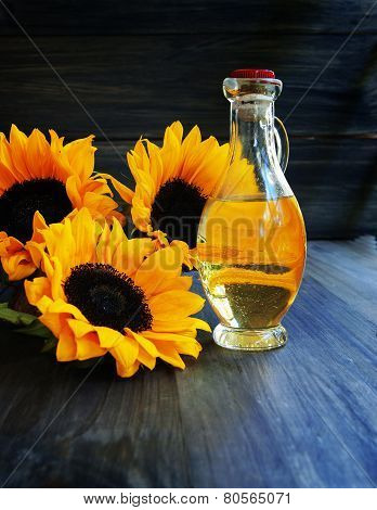 Sunflowers and bottle of oil on a wooden table