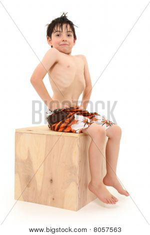 Boy In Swim Suit Sitting On Box