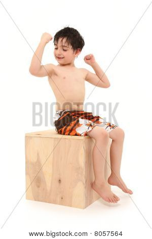 Boy In Swim Suit Sitting On Wooden Box