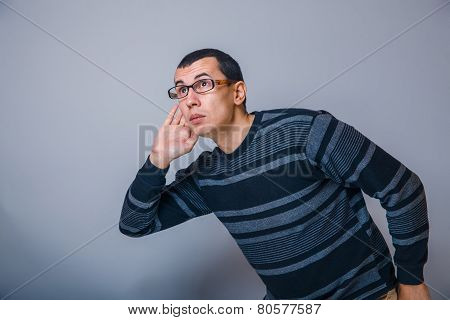 European-looking man years with glasses, overhears