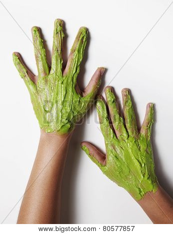 Green Avacado Mask On Awoman's Hands