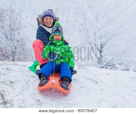 Family having fun with sled in winter park