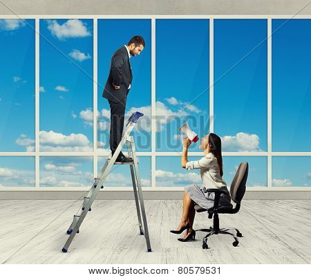 emotional businesswoman with megaphone sitting on chair and screaming at displeased businessman on stepladder. photo in empty room with big windows