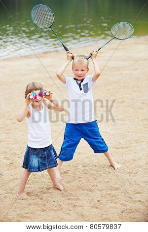 Two happy children playing with badminton equipment on a beach