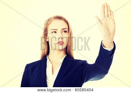 Beautiful business woman is having hand up showing stop gesture.
