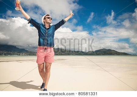 Full body picture of a young happy man on the beach holding both hands in the air celebrating life. He is looking away from the camera while holding a orange cocktail in his right hand.