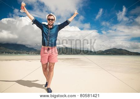 Happy man on the beach looking at the camera while holding both hands in the air. He is holding a cocktail in his right hand.