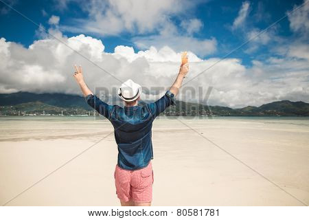 Back view of a young casual man at the seaside holding both hands in the air celebrating life and freedom. He is  holding a cocktail in his right hand.