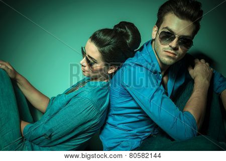 Handsome young fashion man looking at the camera while his lover is leaning on him.