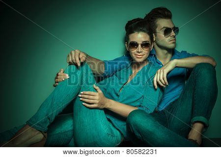 Fashion couple posing on studio background, she is looking at the camera while he is looking away.