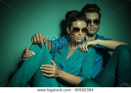 Young fashion man siting near his girlfriend, embracing her. Against studio background.