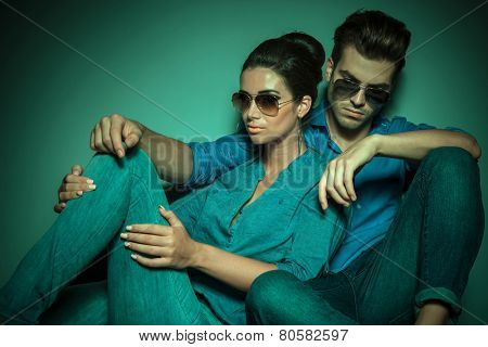 Beautiful young fashion woman leaning on her lover while he is leaning on a wall, looking down thinking.
