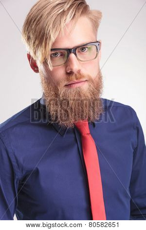Close up picture of a blond beard man wearing a blue shirt and red tie, looking at the camera.