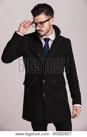Elegant business man taking off his glasses while looking down. On grey studio background.