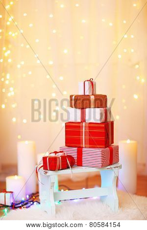 Pile of Christmas present boxes on wooden stool, on bright background