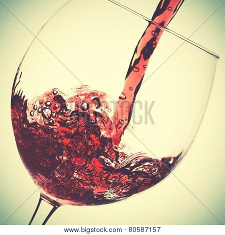 Pouring of red wine in glass. Instagram style filtred image