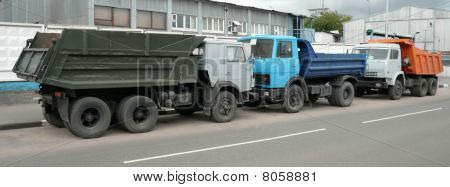 Gray, Blue And Orange Trucks