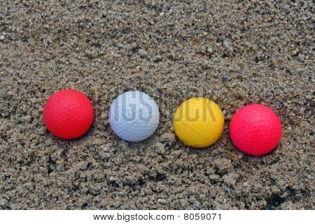 colored golf balls in a bunker