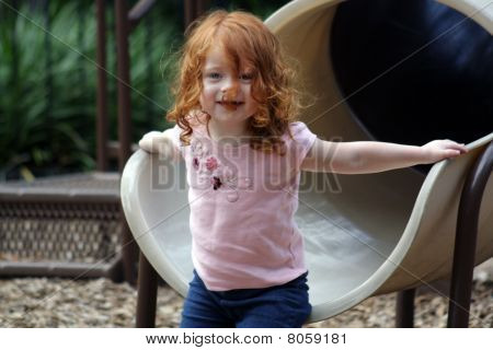 Cute Redhead Girl on a Playground
