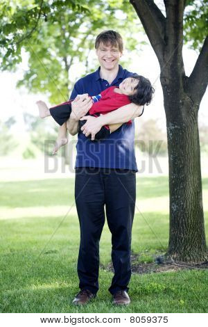 Father holding disabled son outdoors