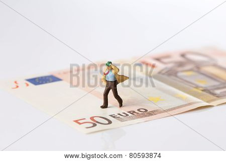 Businessman Figurine Running On A Euro Banknote On White Background
