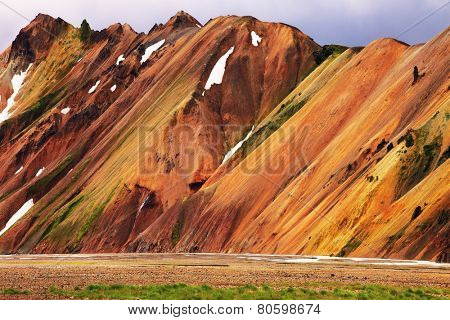 Smooth orange rhyolite mountains in Landmannalaugar nature reserve. In the hollows is last year's snow