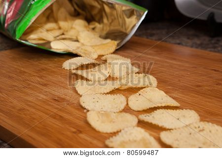 Potato Chips Coming Out Of A Bag Onto A Wood Board